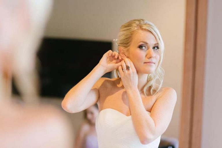 Bride putting earrings on, hair and makeup by Charlotte