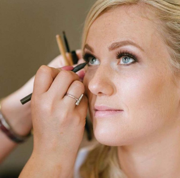 Charlotte applying eyeliner to bridal makeup