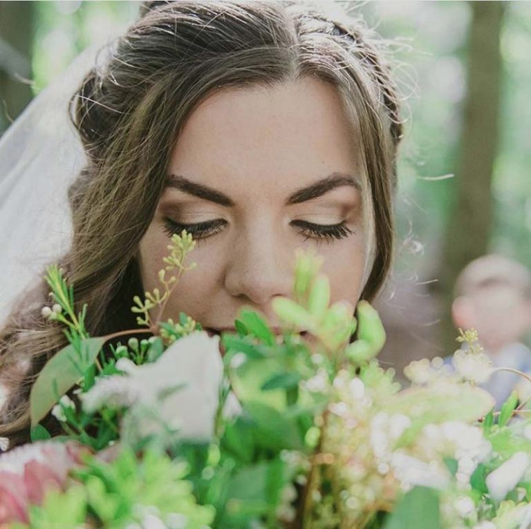 Bride smelling bouquet, makeup by Charlotte