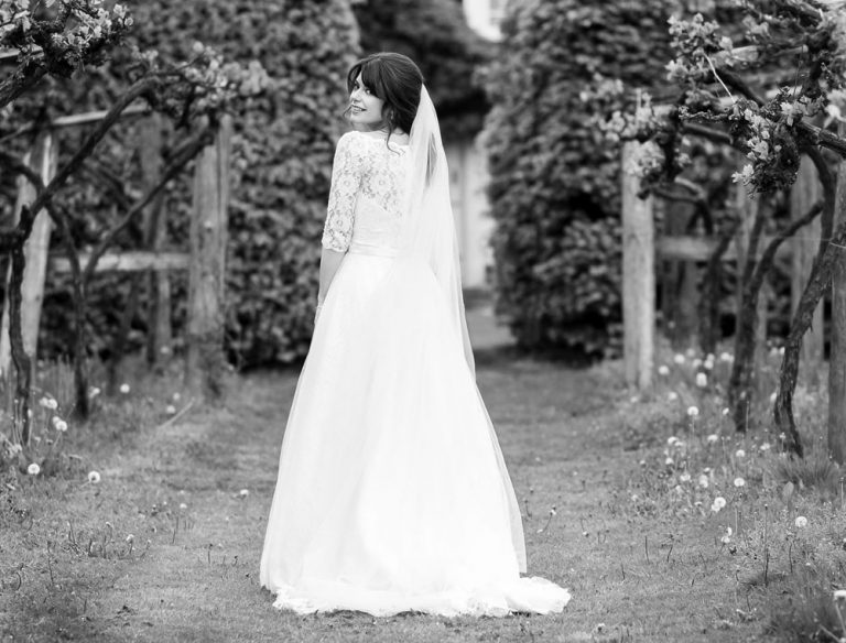 Bride in vine yard with veil, hair and makeup by Storme