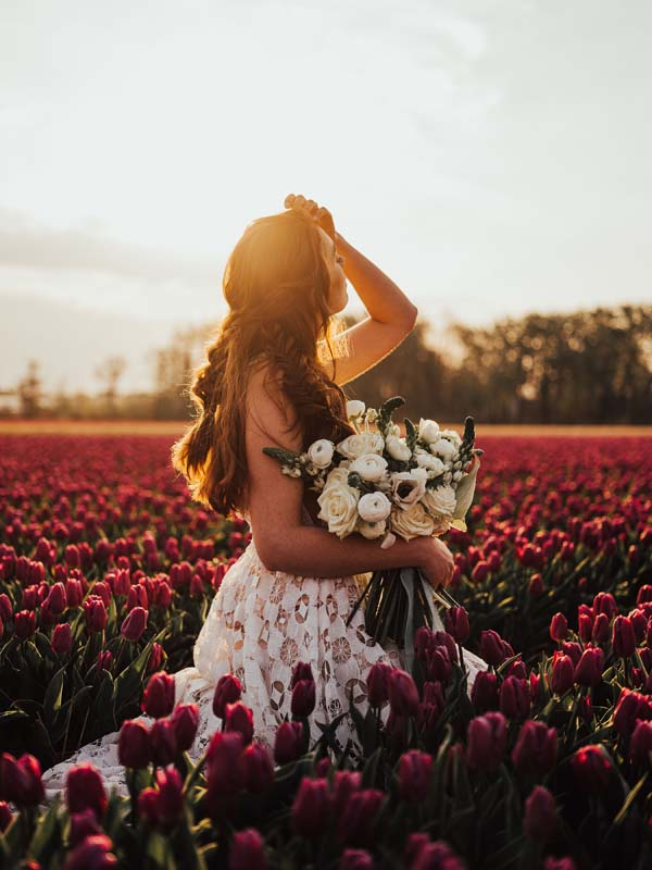 Bride in field of flowers with sun