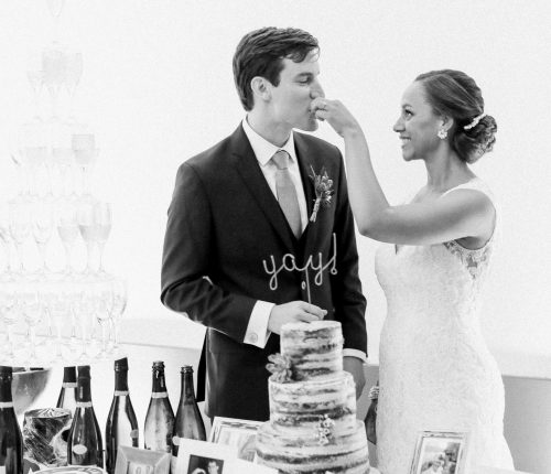 Bride and groom with wedding cake, makeup by Storme