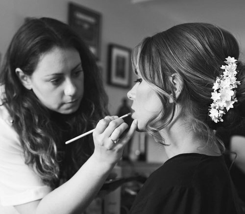 Storme finishing bridal look by applying lipstick